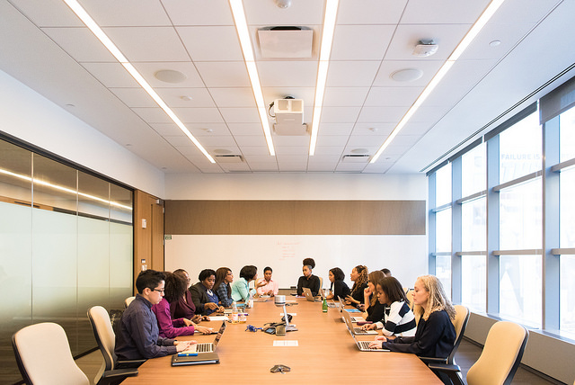 Group of women leaders sitting around a conference table